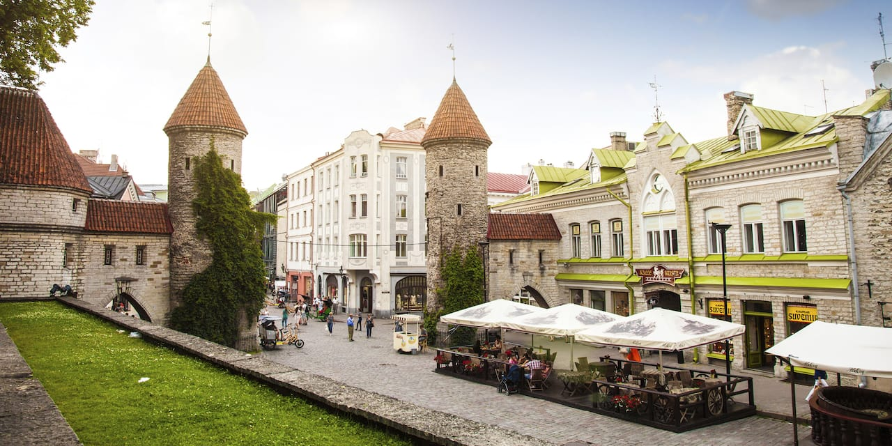 Two spired structures along a building-lined street form the entryway to Old Town Tallinn, Estonia