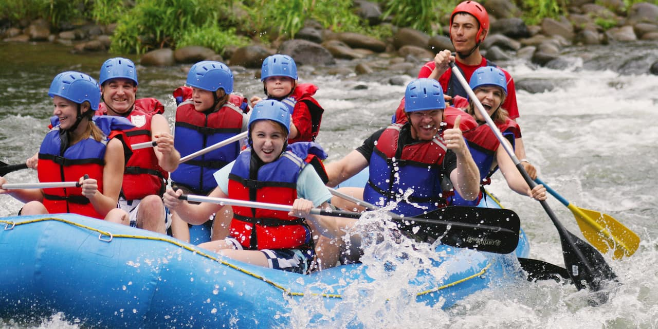 Adults and children paddle as they raft down a river