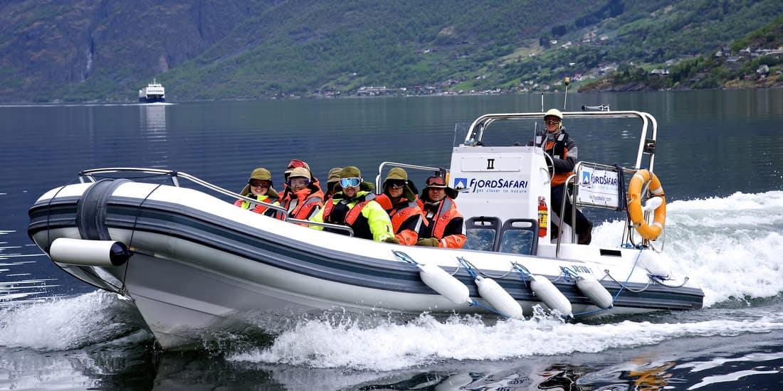 Tourists cruise across a fjord on a rigid inflatable boat