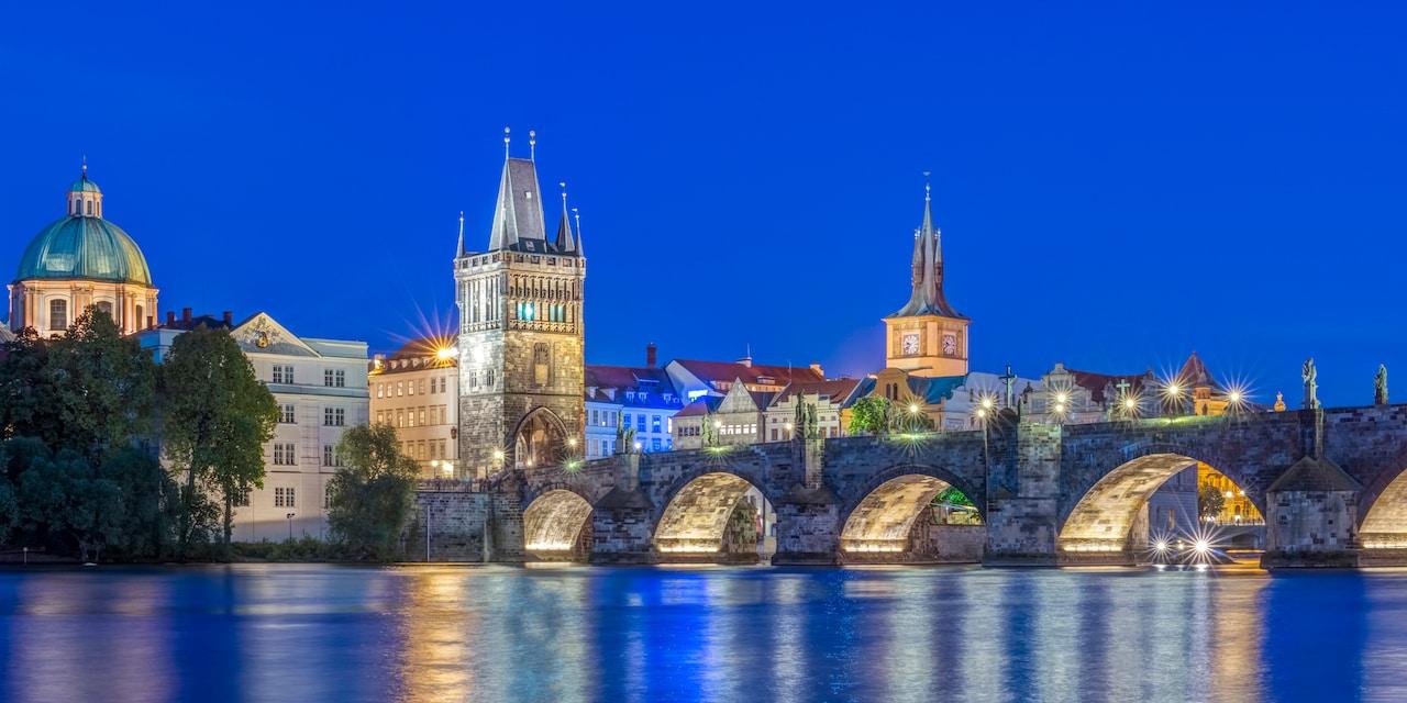 A nighttime image of an illuminated Charles Bridge spanning the Vltava River in Prague, Czech Republic