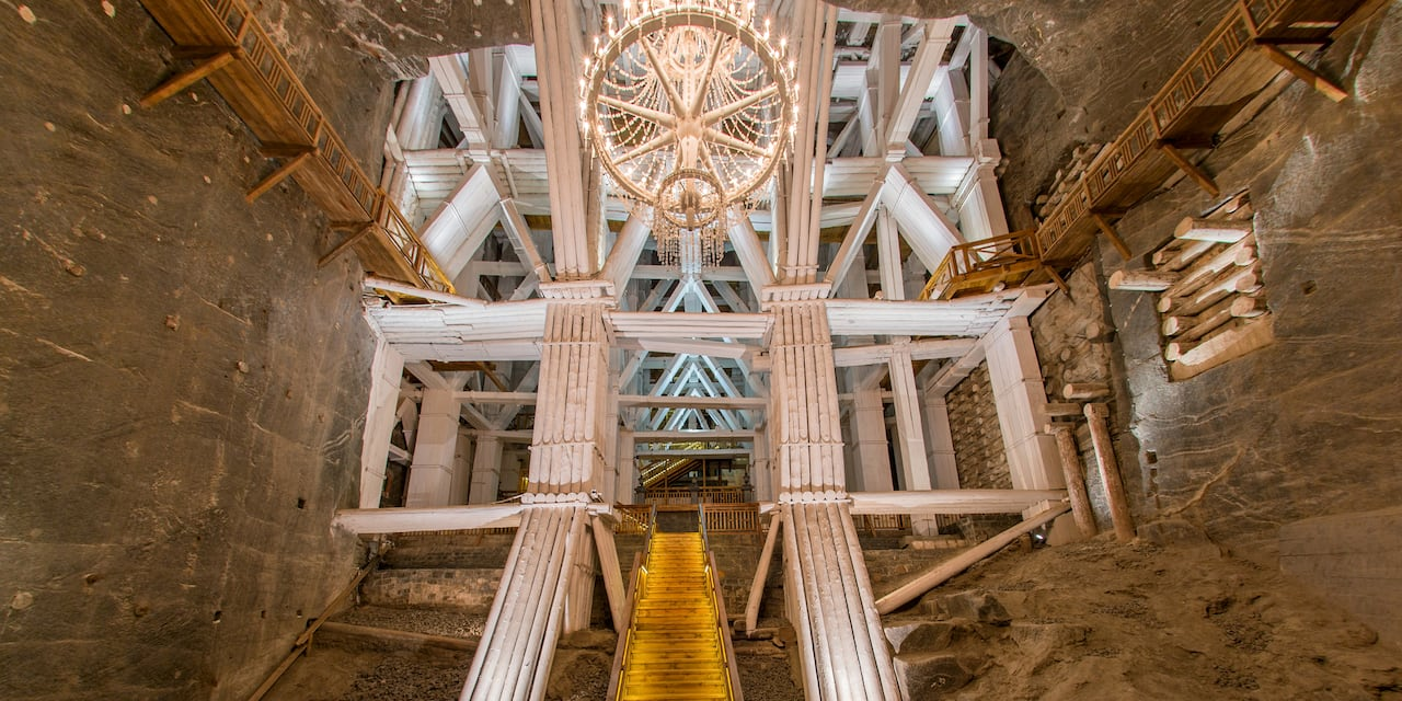 A chandelier hangs from the ceiling amid the interior structures within the Wieliczka Salt Mine