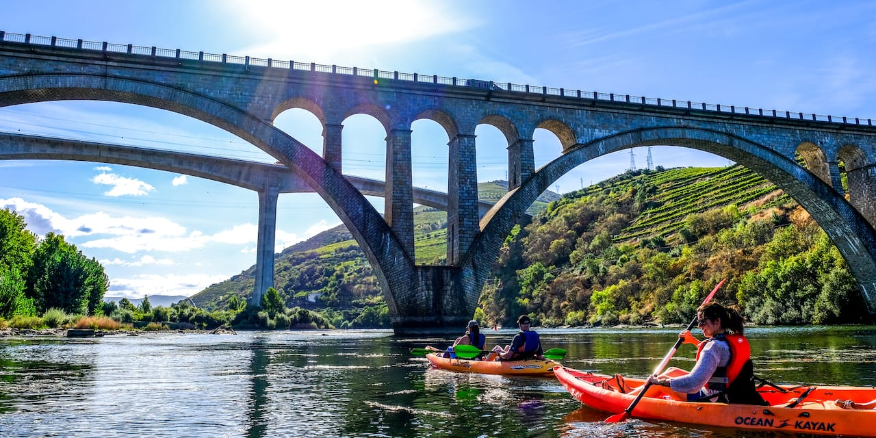 Four people paddle 2 kayaks on a river near an arched bridge
