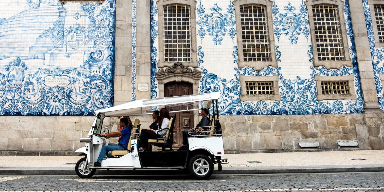A tuk-tuk with several people is parked in front of a tile-covered building