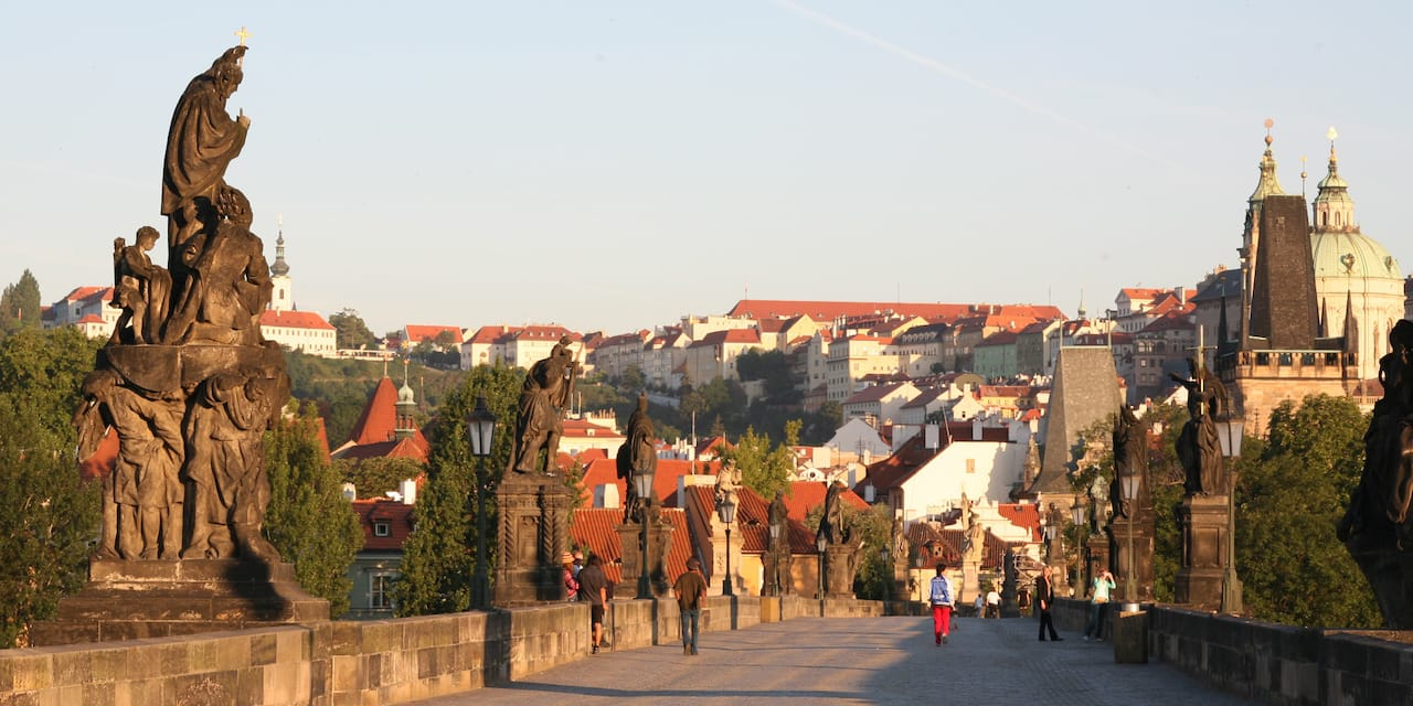 Statues line stone walls on both sides of a bridge