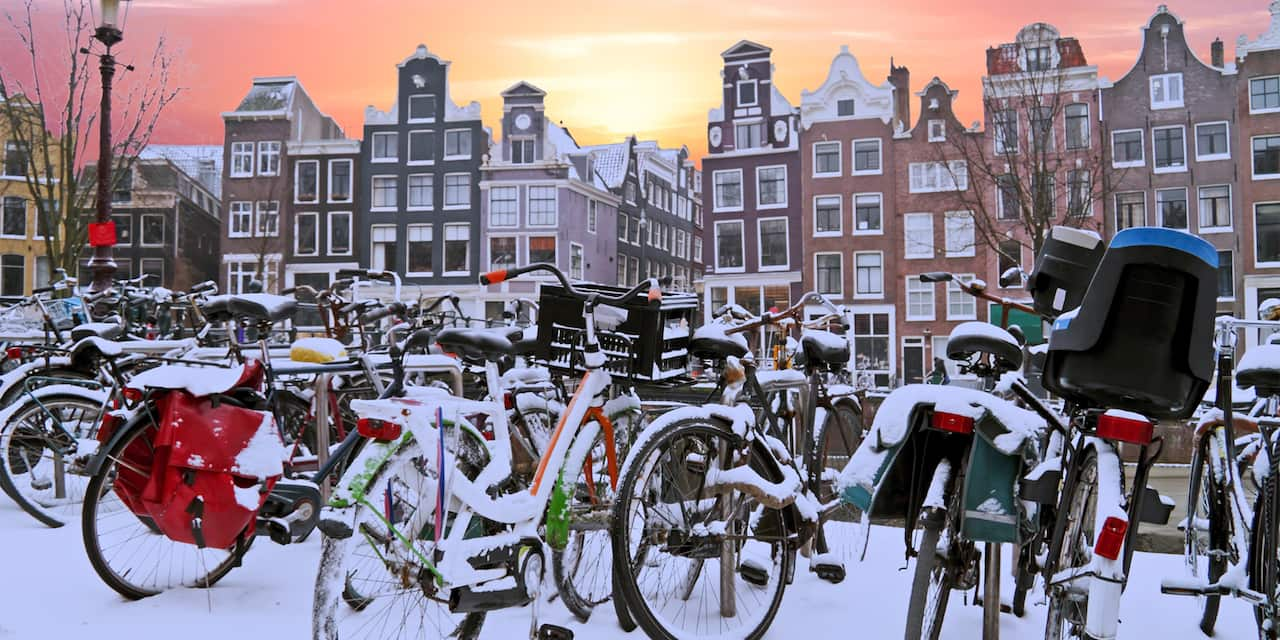 A group of snow covered bicycles parked near a row of buildings in Amsterdam