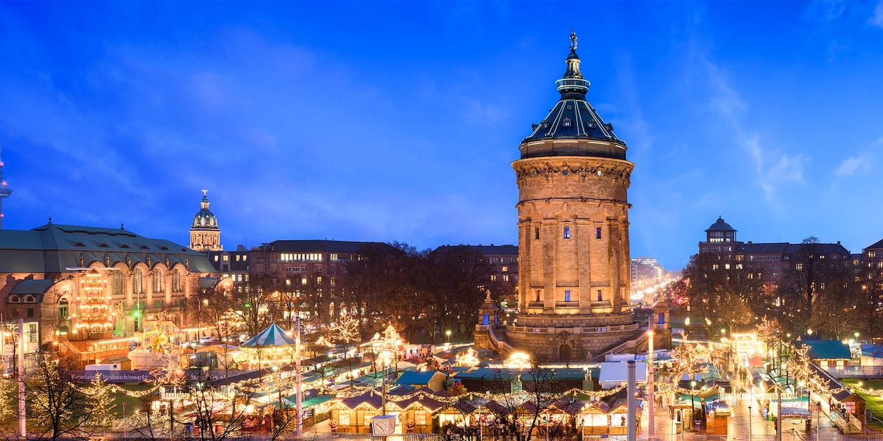 A Christmas market lit up at night near the base of the Water Tower in Manheim, Germany