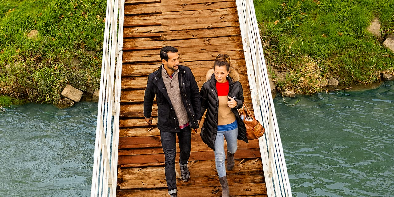 A couple walks across a wooden gangway over the river