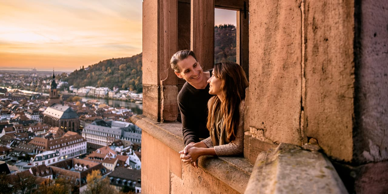A man and woman smile at each other as they lean out a window overlooking an old European town