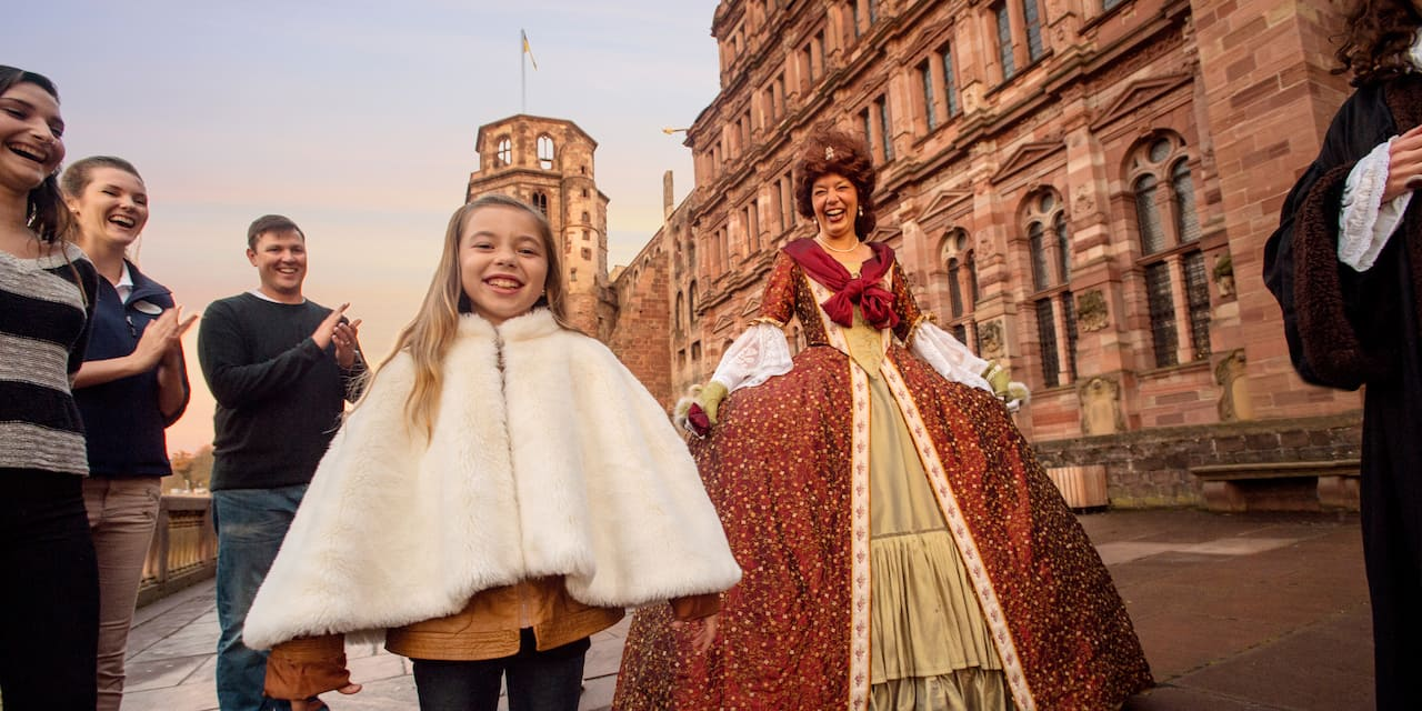 A girl wearing a fur jacket, her family and a woman dressed in a queen's costume outside a castle