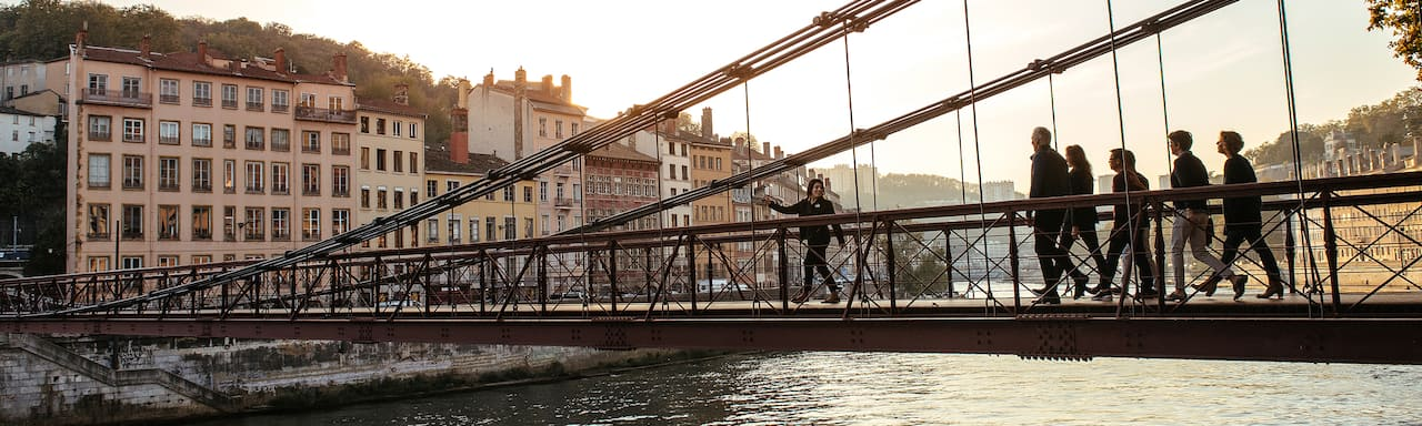 An Adventure Guide leads a group of Adventurers across a bridge spanning the Rhône River