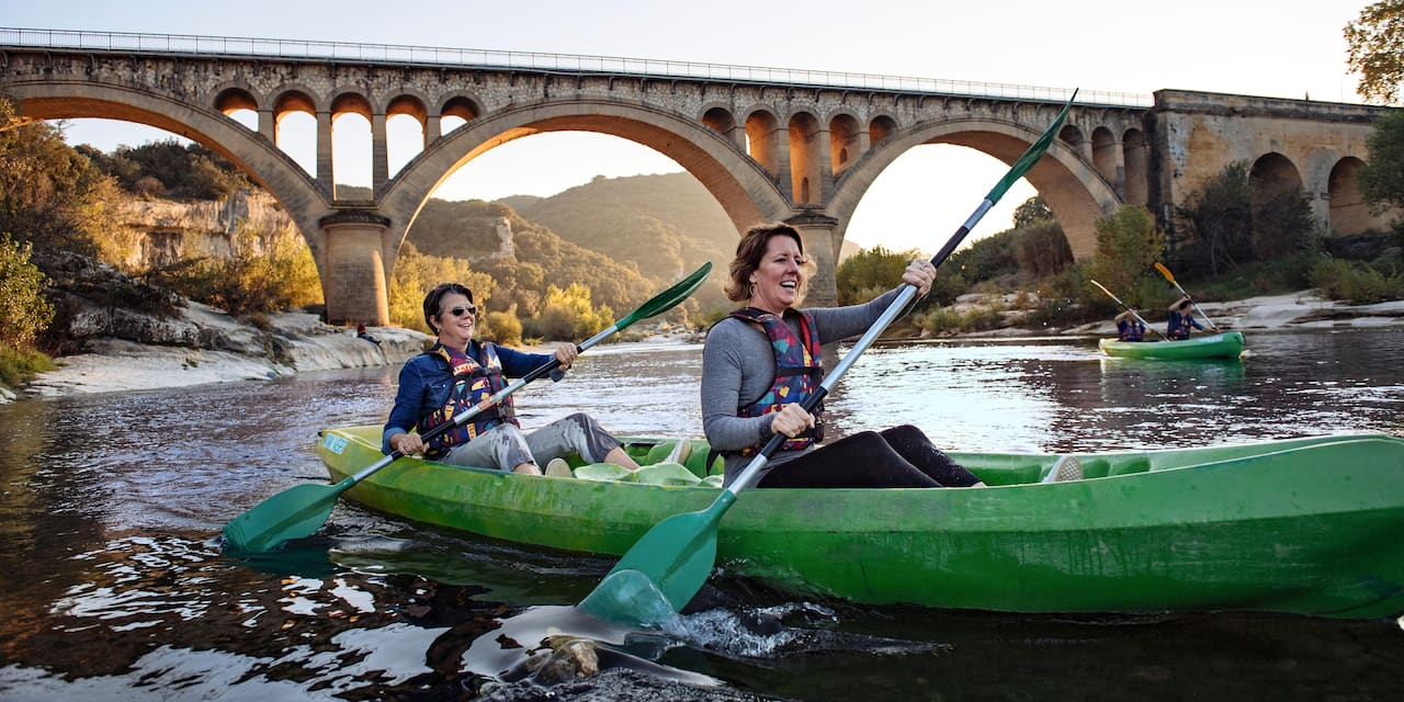 Two women paddle kayaks near the Pont du Gard aqueduct