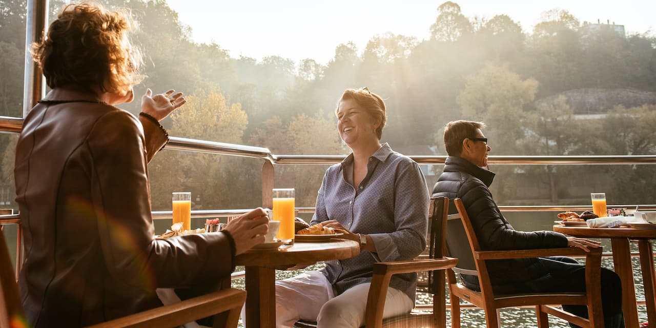 Several Adventurers sit at tables on an outdoor deck aboard a river cruise ship
