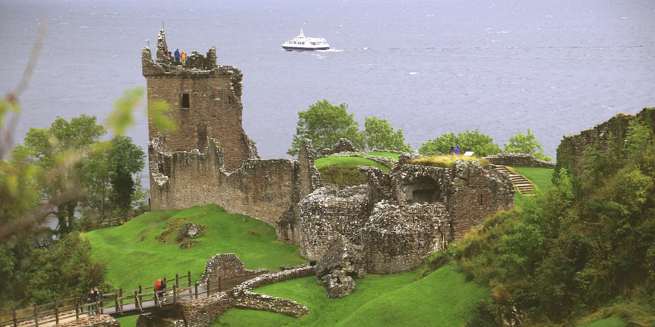 The ruins of Urquhart Castle on a grass covered hill overlooking Loch Ness with a boat in the distance