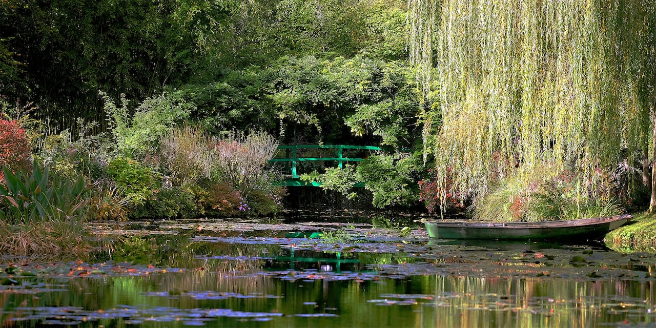 A rowboat sits in the pond amongst the gardens at the house of Claude Monet in Giverny, France