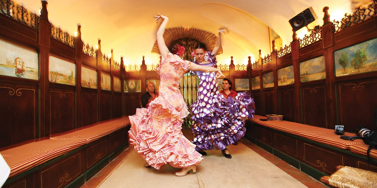 Two female flamenco dancers perform in traditional dress