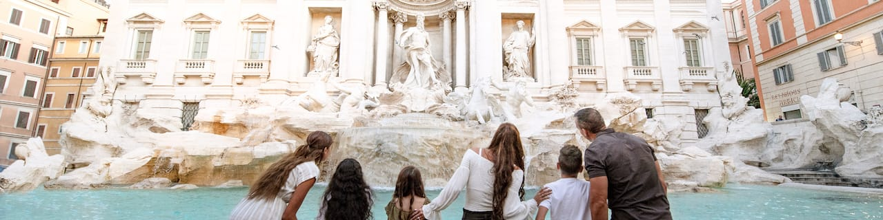 A family of six stands in front of the Trevi Fountain