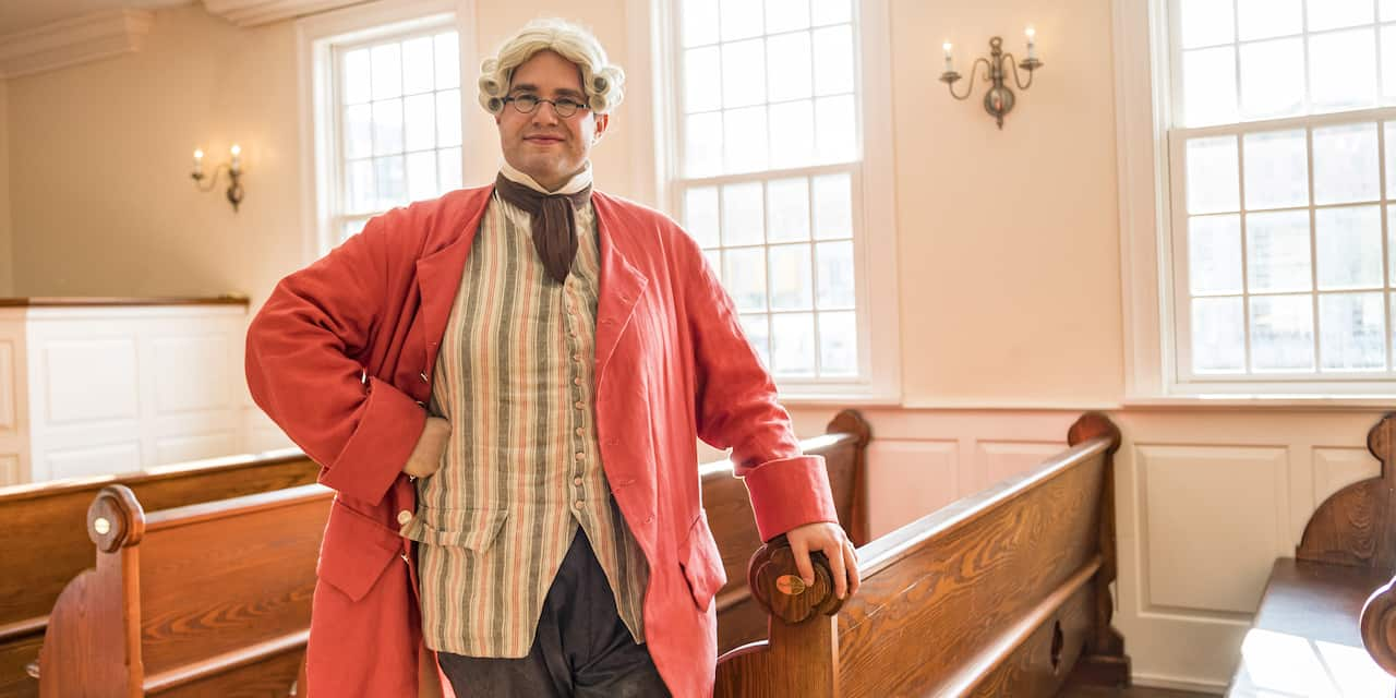 A historical reenactor dressed in colonial attire strikes a pose inside a church