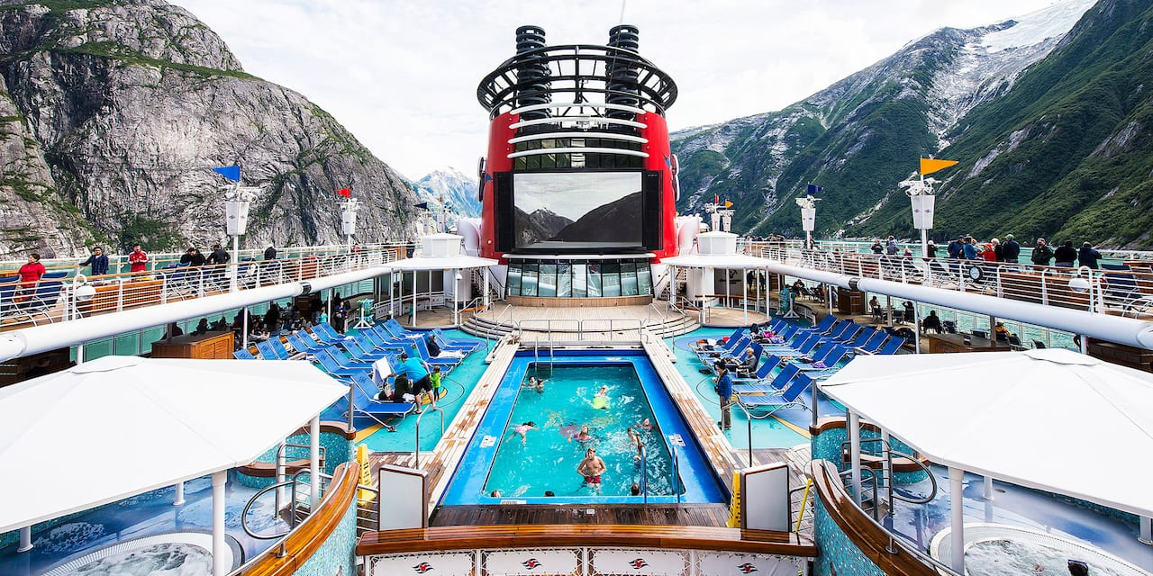 The pool and top deck area of the Disney Wonder cruise ship as it passes through a stretch of mountains