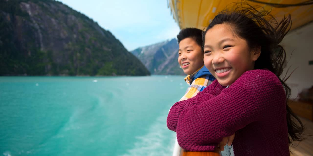 A young girl and boy are all smiles as they look at moutains and the ocean from a railing on a deck of the Disney Wonder cruise ship