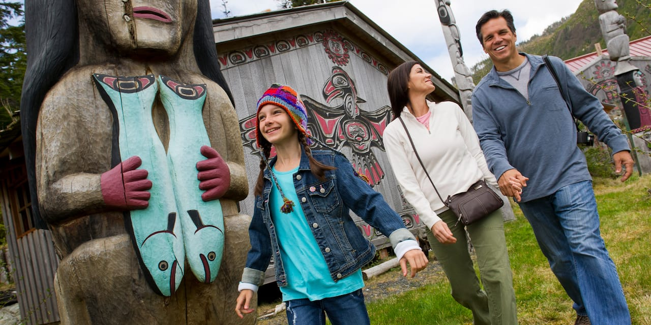 A man, woman and their young daughter walk amongst carved totem poles in Ketchikan, Alaska