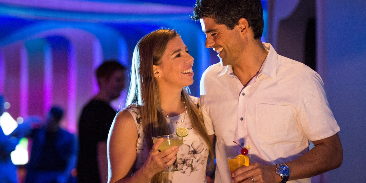 A young couple hold drinks and smile as they look into each other's eyes