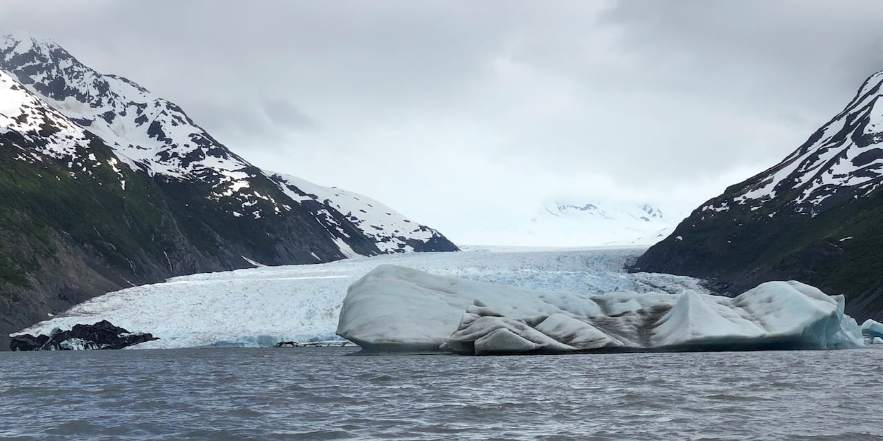 Spencer Glacier floating in a lake amid snowy mountains