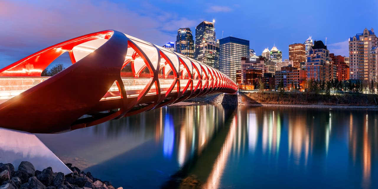 The modern Calgary footbridge with the city's skyline in the background at night