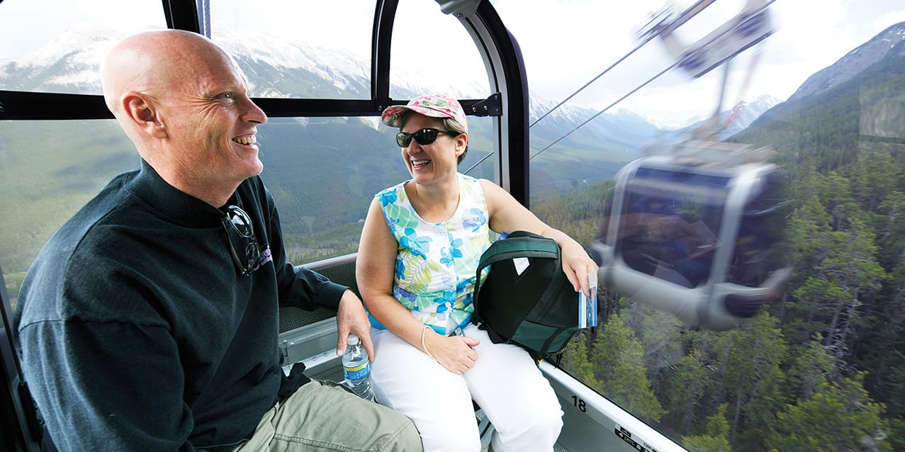 A couple rides a gondola up the side of snowy Sulphur Mountain