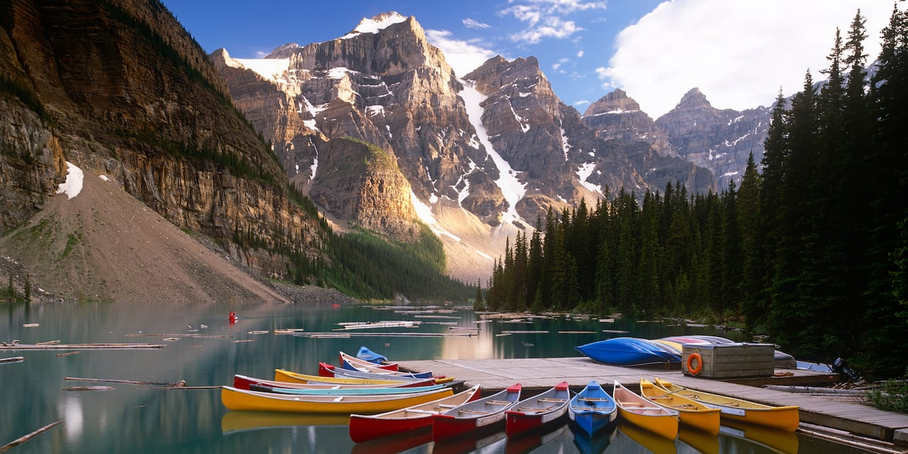 A dozen canoes rest at a dock on a lake surrounded by mountains and pine trees