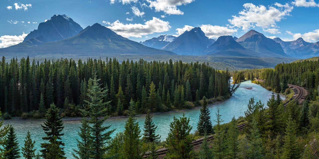 The tree-lined Bow River at the base of mountains