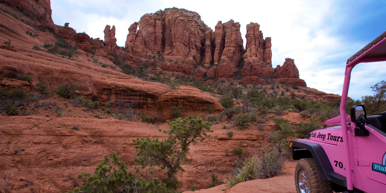 An off-road jeep faces buttes and rock formations