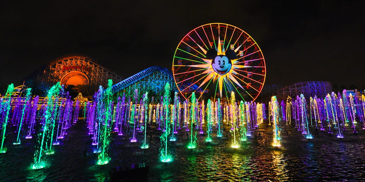 Fountains of water spray into the nighttime air with a large wheel with Micky Mouse's face in the background