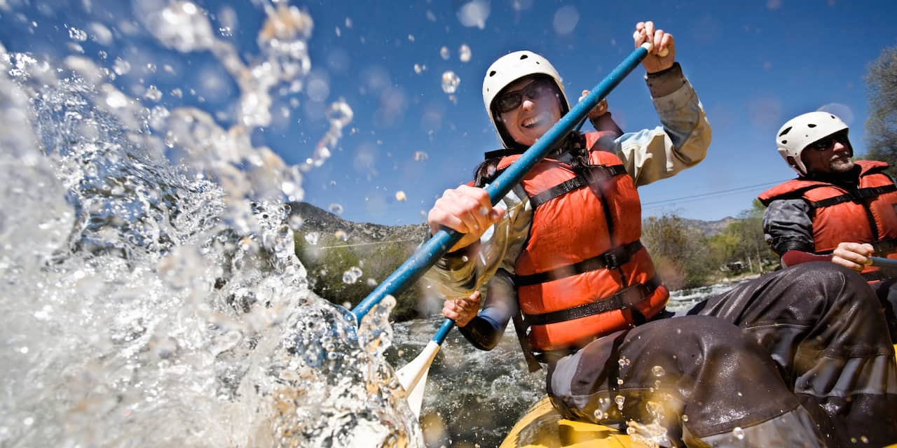 3 people whitewater rafting in rapids