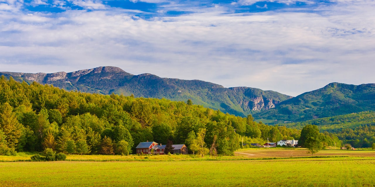 Two New England farms nestled between open fields and lush forest near the base of Mount Mansfield in the background