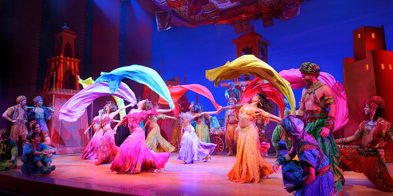 Cast Members dance on stage with scarves in Disney's Aladdin: The Hit Broadway Musical