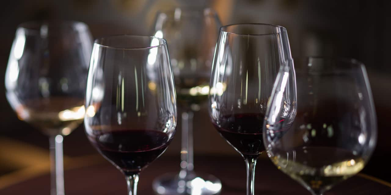 Five wine glasses containing assorted wines