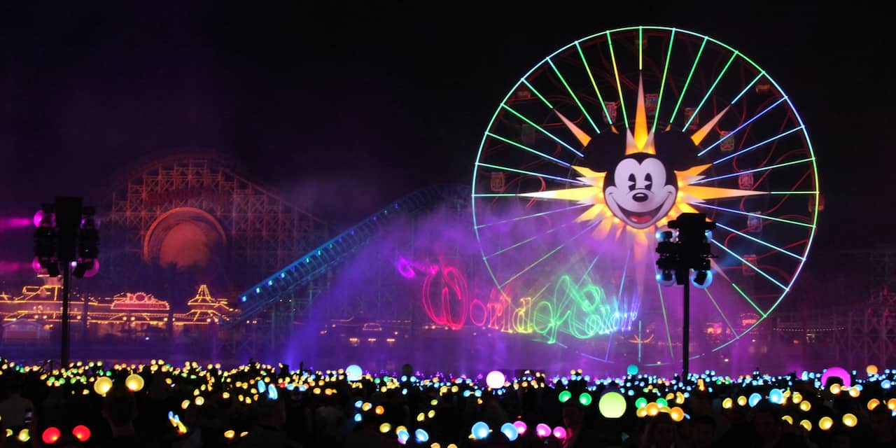 A crowd of people wearing light-up Mickey Mouse ears watch the colors and mists of the World of Color show by Mickey's Fun Wheel at Disney California Adventure