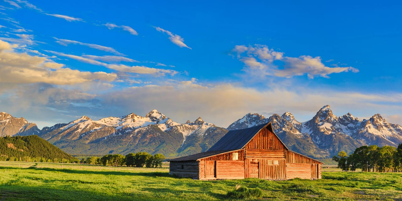 A barn amid a field with snow capped mountains in the background