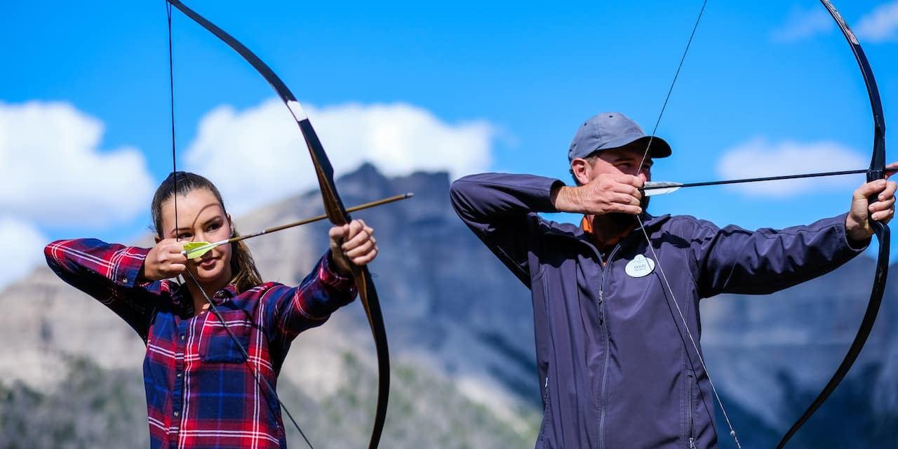 A man and a woman take aim with bows and arrows while shooting archery