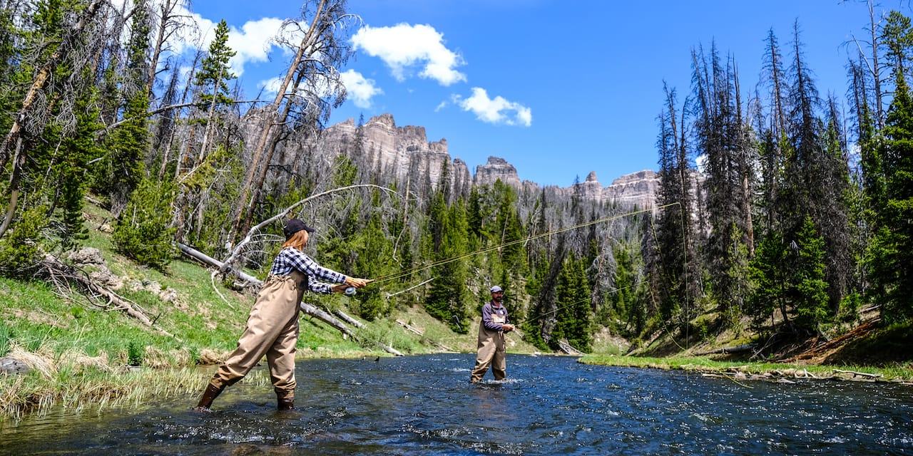 Two people wearing waders fly fish in a river