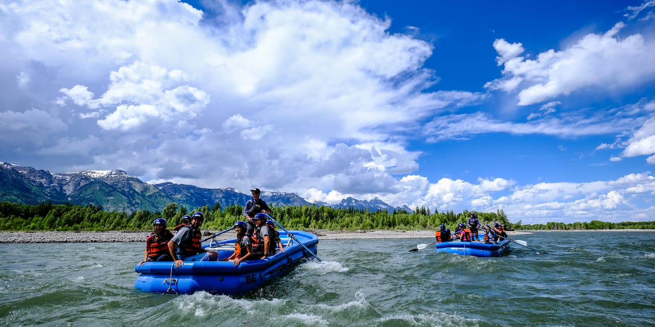 Two rafts filled with people, each paddled by a guide, ride through rapids on a river