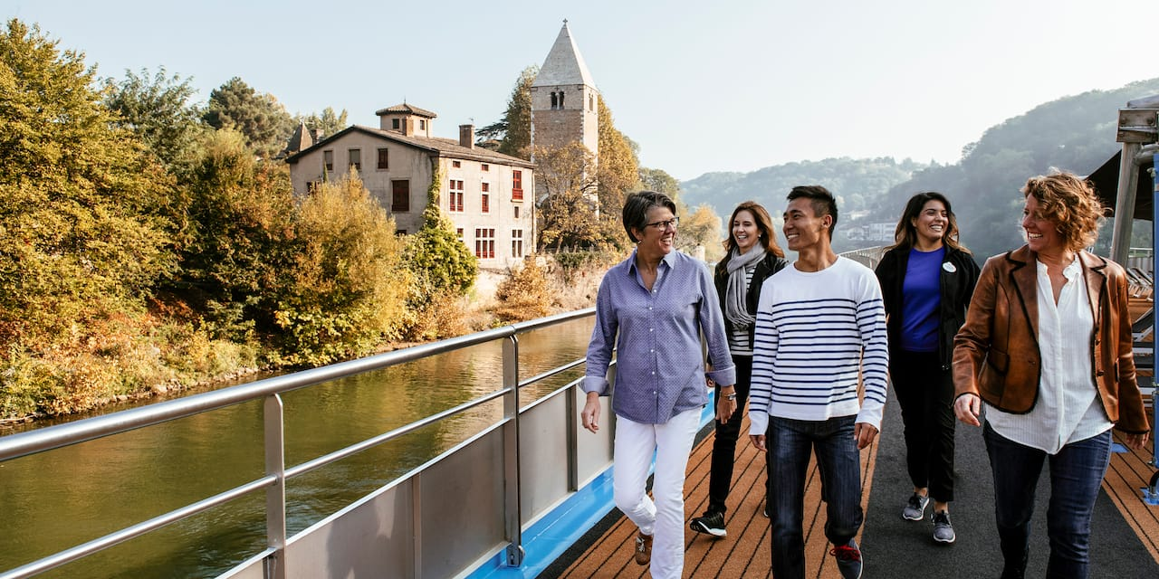 A group of 5 people walk along the deck of a ship as it passes an old building on a nearby riverbank