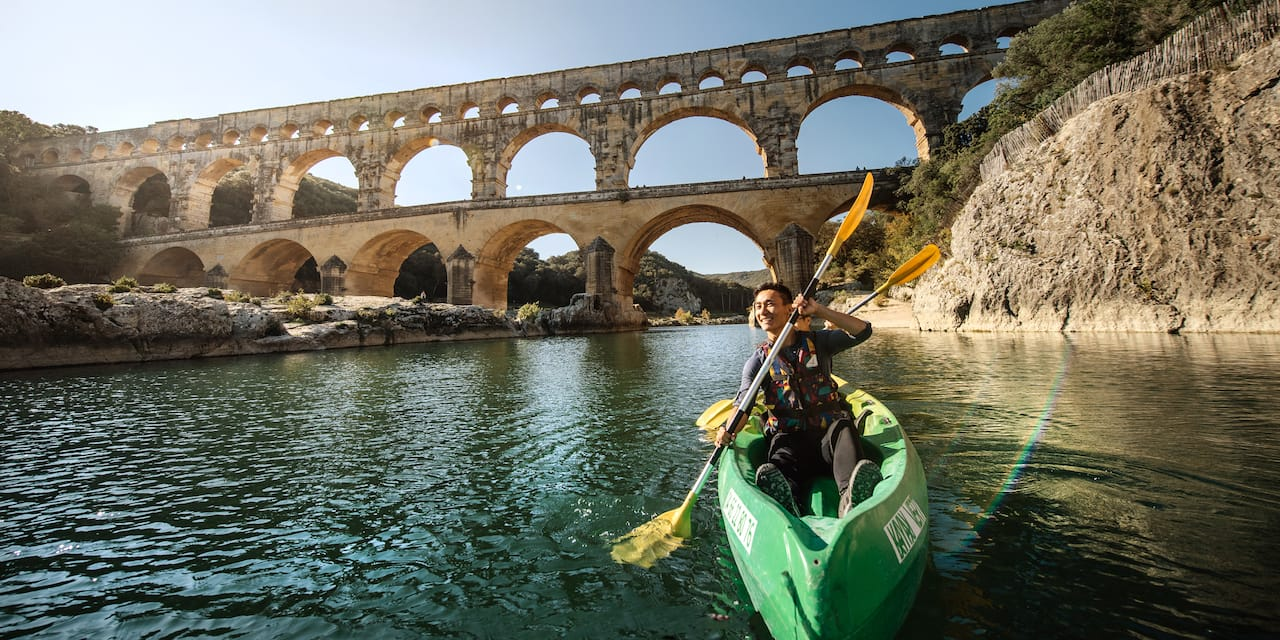 Two people kayak near the Pont du Gard aqueduct on the River Gard in Avignon, France