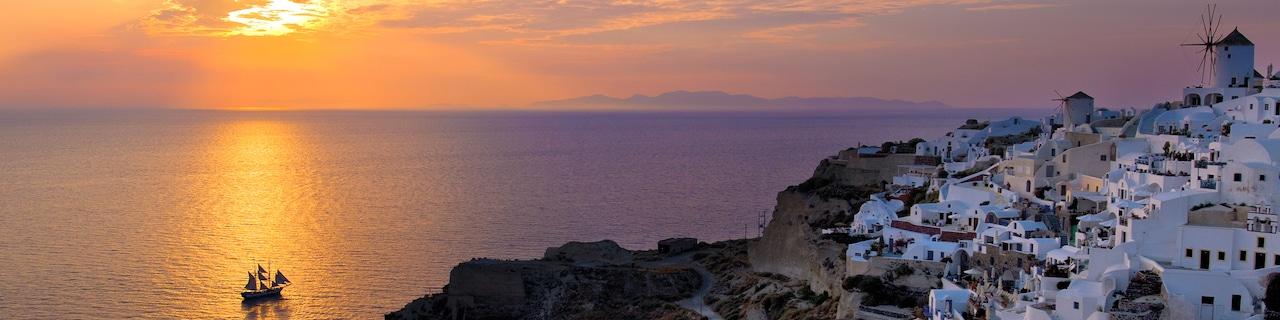 The sun goes down on the horizon near Santorini, Greece