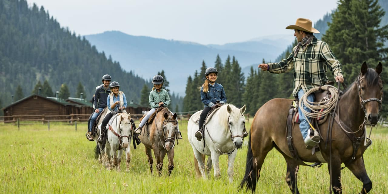 A cowboy leads a family on horseback