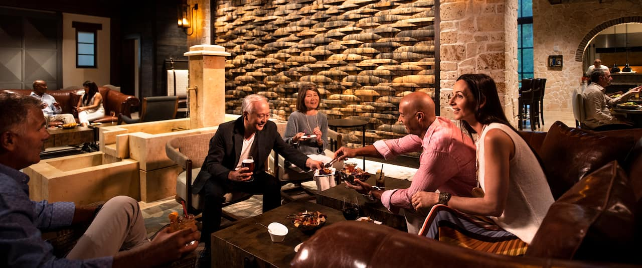 Two couples smile and socialize as they sit in a lounge area