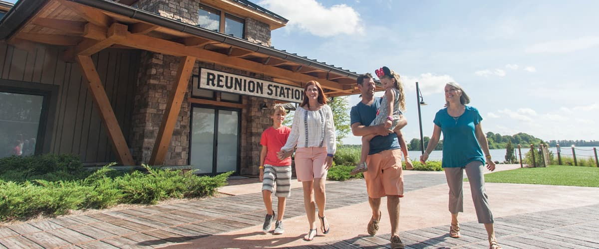 A family of 5 walks in front of Reunion Station and a lake at Disney's Wilderness Lodge