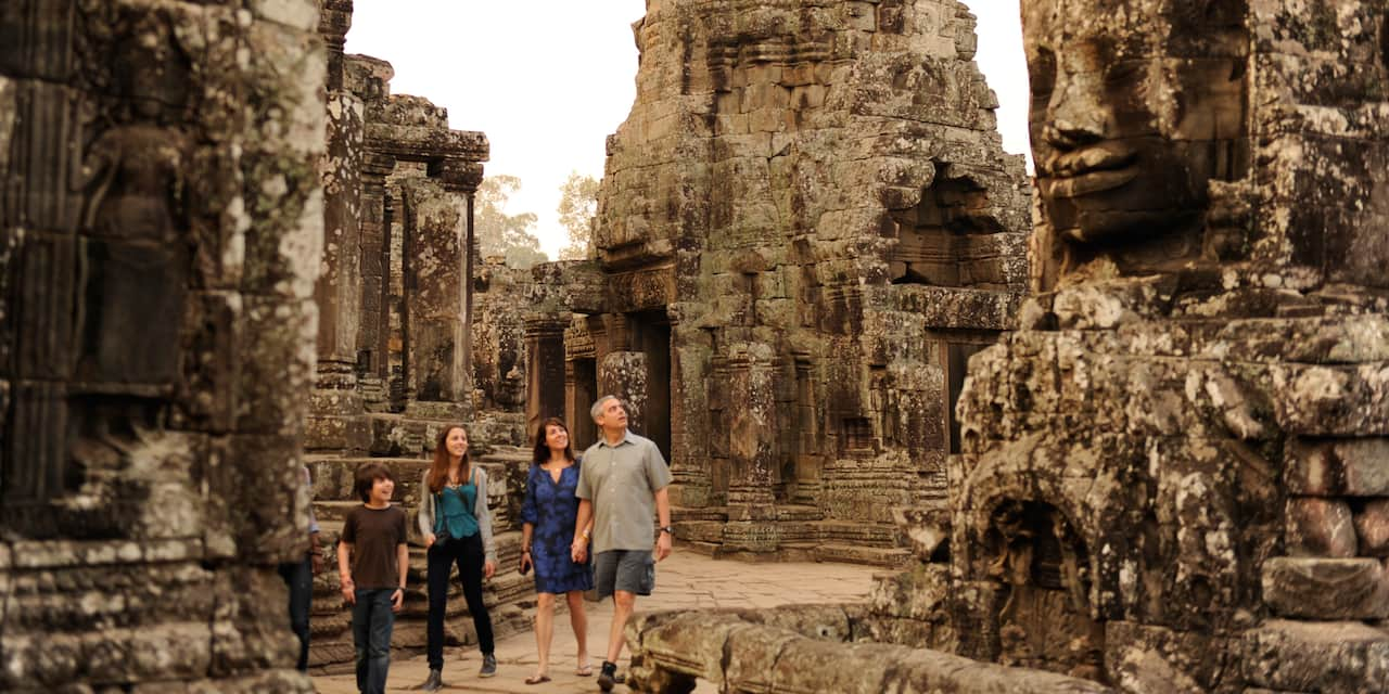 A family of 4 walks through towering ruins