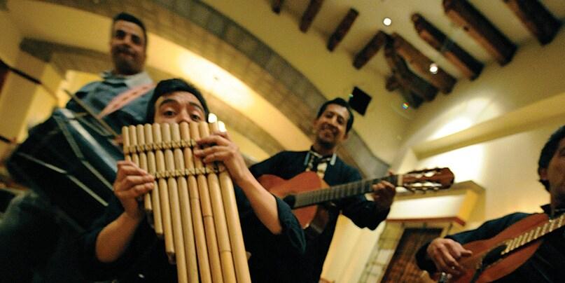 4 Ecuadorian musicians playing guitars and a pan flute
