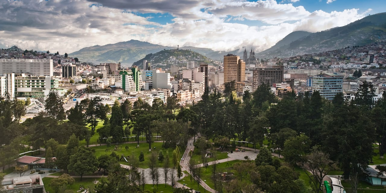 A park at the heart of downtown Quito, Ecuador surrounded by mountains and clouds